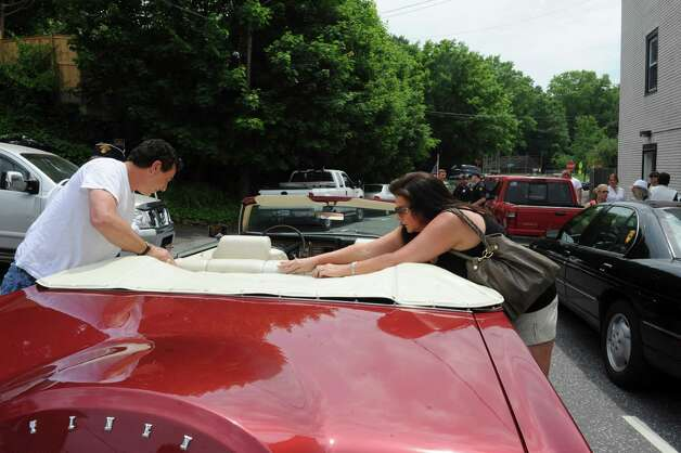 C J Porricelli and his wife Michelle, of Classic Auto Body of Greenwich, get ready their 1973 Lincoln so that veterans could ride during the Byram Veterans Association's Memorial Day Parade Sunday, May 27, 2012. Photo: Helen Neafsey / Greenwich Time
