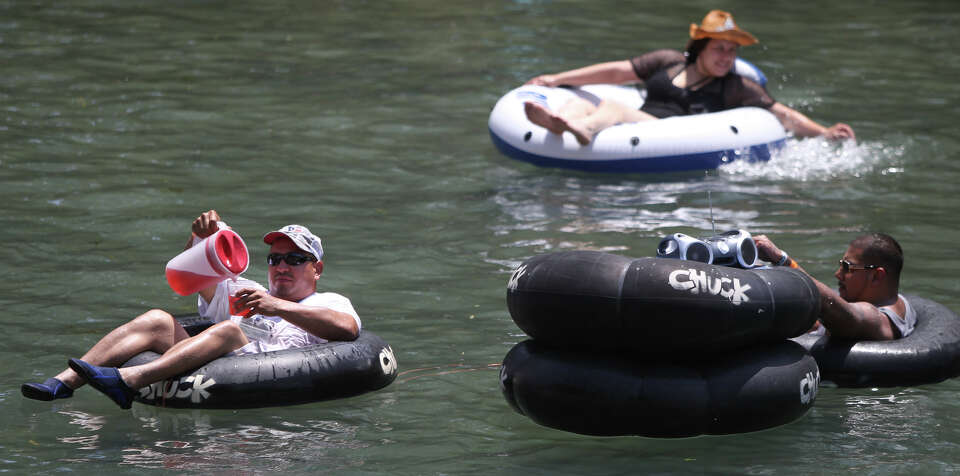 A man (left) pours himself a beverage from a pitcher while floating down the Comal River in New Brau