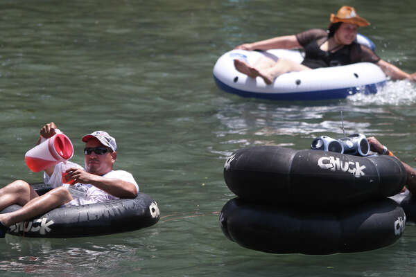 A man (left) pours himself a beverage from a pitcher while floating down the Comal River in New Braunfels Memorial Day. Disposable containers such as beer cans are no longer legal for tubers to carry down the Comal river in the city of New Braunfels.