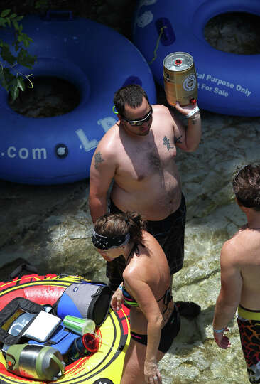 A man holds what appears to be a large can of Warsteiner German beer while taking a break from tubin
