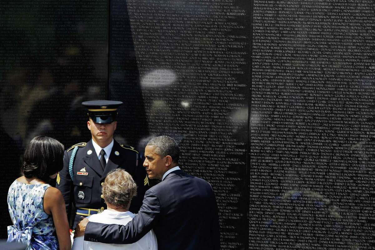 President Barack Obama, right, and Michelle Obama, left, help Rose Mary Sabo-Brown at the Vietnam Veterans Memorial during a Memorial Day ceremony on the National Mall Tuesday in Washington, DC.