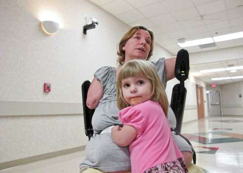 Two year-old  Arielle Hayes rides on her mother's wheelchair  as Katy Hayes departs from her radiology appointment  Tuesday 22, 2012 at Kingwood Medical Center in preparation for her arm transplants. Photo: Billy Smith II, Chronicle / © 2012 Houston Chronicle