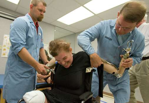 (left) Certified Prosthetist Sonny Wiggins and (right) Ted Muilenburg, practitioner and the president of Muilenburg Prosthetics, fit (center) Katy Hayes with her new conventional prosthetic arms Thursday, June 24, 2010, at Muilenburg Prosthetics in Houston, Texas.  After hearing of Katy's story  Ted Muilenburg donated the prosthetic arms to Katy Hayes.   Shortly after the birth of Katy's daughter, Arielle, Katy Hayes began to experience intense pain and went to the local hospital. She is currently battling for her life after a series of complications resulting from a Streptococcal A infection. As a result, Katy has experienced multiple organ failure and the loss of her arms and legs. Photo: Billy Smith II, Houston Chronicle / Houston Chronicle
