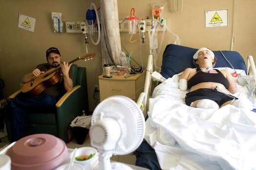 (l-r) Al Hayes a music teacher at Pin Oak Middle school plays his guitar as his wife Katy Hayes, rests in bed Wednesday, May 5, 2010 in the Acute Care area of Parkland Hospital in Dallas, Texas. On February 10, 2010  Katy and Al Hayes had their third child, Arielle. but just days after the baby's birth, Katy experienced intense abdominal pain and was rushed to the hospital. There, the Hayes's discovered that Katy had been infected with Streptococcal, an infection that causes aggressive toxins to multiply and cause damage to tissues and organs.  To save her life, doctors performed a dozen surgeries, including amputating both arms and legs above the middle joints. Photo: Billy Smith II, Houston Chronicle / Houston Chronicle