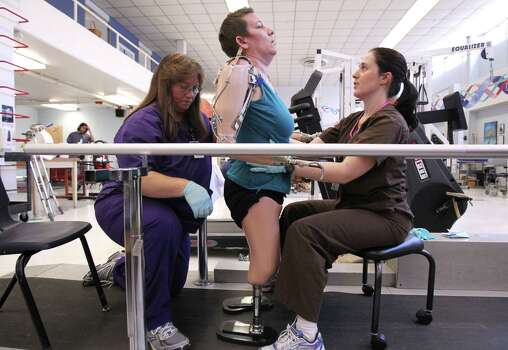 (center) Katy Hayes stands and walks on her short non-articular pylon prosthesis with the help of (l-r) Jamie Lottinger and Heather Zissman physical therapist at The Institute for Rehabilitation and Research Memorial Hermann, in Houston, Texas, Thursday, September 16, 2010. After the birth of Katy Hayes daughter, Arielle, Katy began to experience a series of complications resulting from a Streptococcal A infection. As a result, Katy experienced multiple organ failure and the loss of her arms and legs. Hayes is currently in the first week of a two week intense physical therapy program. Hayes now in 24 hour care at TIRR Hermann Memorial is spending at least three hours a day on physical and occupational therapy. Photo: Billy Smith II, Houston Chronicle / Houston Chronicle