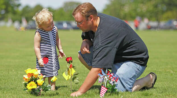 Lindsey Lewis, 2, watches her dad, Steven Lewis, place a rose on the grave of his dad, Troy Lewis Jr. (a Navy WWII vet) after the Memorial Day ceremony at the Houston National Cemetery, Monday, May 28, 2012, in Houston. Photo: Karen Warren, Houston Chronicle / © 2012  Houston Chronicle