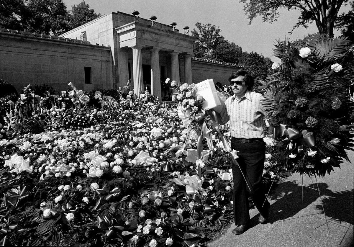 FILE - In this Aug. 18, 1977 file photo, a florist adds more floral arrangements to the overflowing collection of flowers that cover the ground at the mausoleum where singer Elvis Presley will be entombed during funeral services today in Memphis, Tenn. Celebrity auctioneer Darren Julien says the crypt inside the granite and marble mausoleum where Presley was originally entombed at the Forest Hill Cemetery in Memphis, Tenn., will be part of his