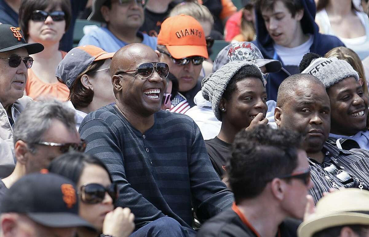 Former baseball player Barry Bonds laughs as he watches a baseball game between the San Francisco Giants and the Arizona Diamondbacks in San Francisco, Monday, May 28, 2012.