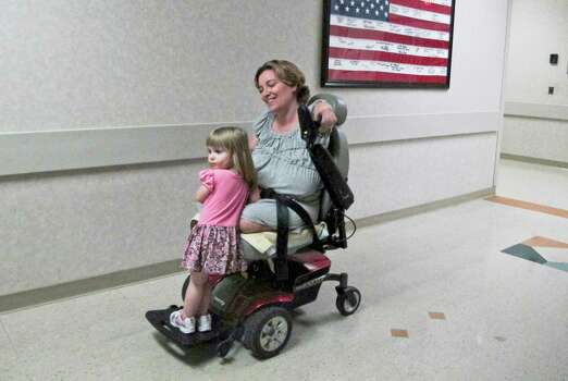 Two-year-old Arielle Hayes  rides with her mother, Katy Hayes, after a radiology appointment  last week at Kingwood Medical Center. Katy lost her limbs to a flesh-eating infection soon after Arielle's birth. Photo: Billy Smith II / © 2012 Houston Chronicle