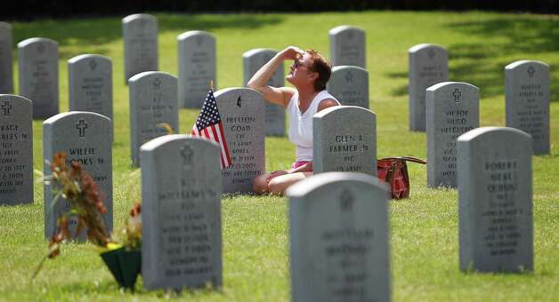Debbie Hinojosa sits at the grave of her father, Preston Goad, on Memorial Day at Houston National Cemetery. Goad