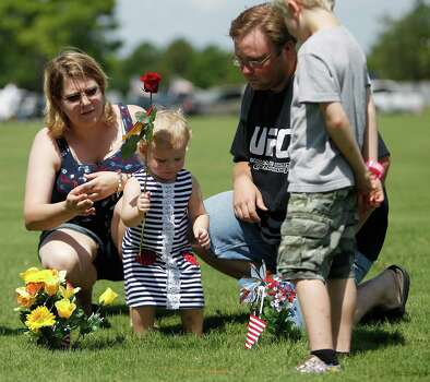 Lindsey Lewis, 2, has a rose for the grave of her great-grandfather, Troy Lewis Jr., a World War II veteran. With her at Houston National Cemetery are her aunt, Sandra Lott-Tyburczyk,  her dad, Steven Lewis, and cousin, Tyler Tyburczyk, 9. Photo: Karen Warren / © 2012  Houston Chronicle