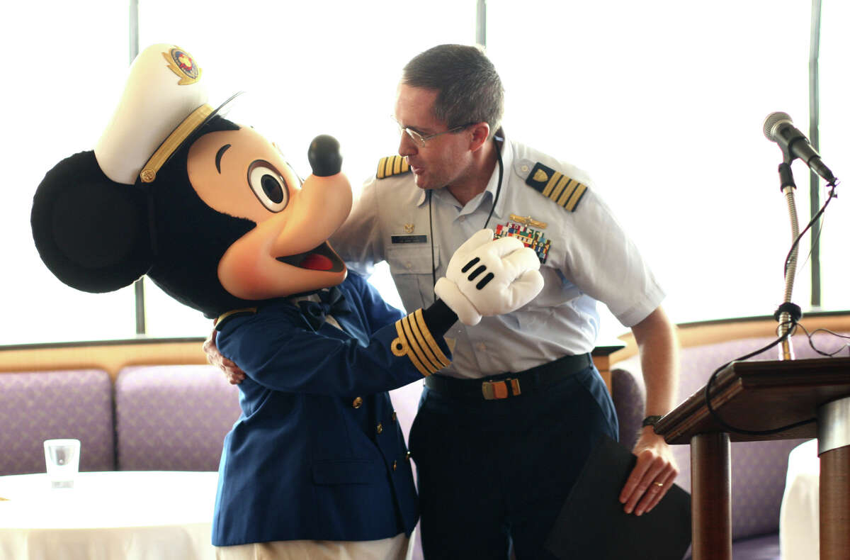 U.S. Coast Guard Capt. Scott Ferguson, who is in charge of of Coast Guard Sector Puget Sound, embraces Mickey Mouse during an inaugural call ceremony aboard the Disney's cruise ship Wonder on Monday, May 28, 2012 in Seattle. On Monday the ship made its first stop in Seattle. The cruise liner will be based out of Seattle for the next 14 weeks.