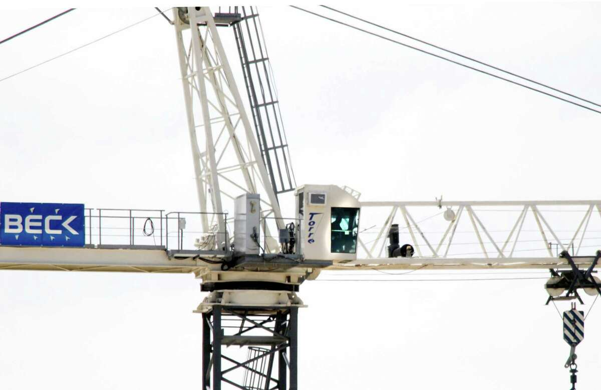 A man sits in a crane 150 feet above the Southern Methodist University campus in Dallas, threatening to shoot the Dallas Police officers trying to talk him down, Monday, May 28, 2012. Special tactics officers from the Dallas Police Department were working with SMU campus police to manage the scene and try to talk the man down from the crane. No injuries had been reported. (AP Photo/The Dallas Morning News, David Woo)