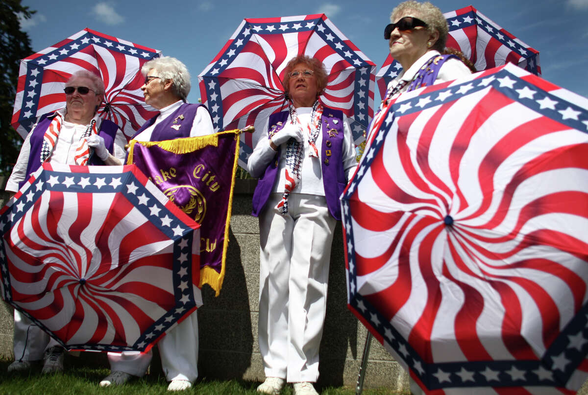 Members of the Lake City Emblem Club, from left, Ethel LaRose, Opal Johnson, Dianne Salmonsen, and Betty Edwards wait to parade during the annual Memorial Day celebration at Evergreen-Washelli Seattle Veterans' Memorial Cemetery on Monday, May 28, 2012. The event was the 86th annual Memorial Day celebration held at Evergreen-Washelli.
