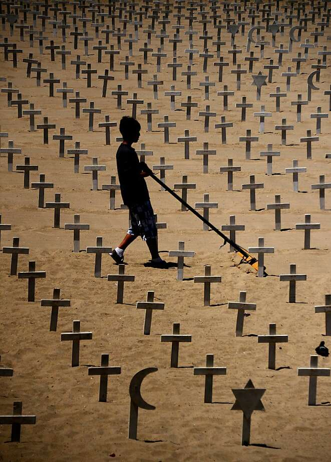 "A boy sweeps sand at Arlington West Memorial built on the beach next to Santa Monica Pier in  Santa Monica,California on May 28, 2012. Arlington West refers to the ""temporary cemetery"" itself, as well as Veterans for Peace's project of installing the temporary memorial. The name, Arlington West, was given to the memorial by WWII veteran Ted Berlin and reflects the name of the national cemetery of the United States, Arlington National Cemetery, a burial place of honor for fallen war heroes. Arlington National Cemetery is the location of the Tomb of the Unknown Soldier, and is also the final resting place for John F. Kennedy. Arlington West—in a manner similar to ""real"" cemeteries—is intended by the project organizers to be a place to mourn, reflect, contemplate, grieve, and meditate, to honor and acknowledge those who have lost their lives, and to reflect upon the costs of war. Photo: Joe Klamar, AFP/Getty Images"