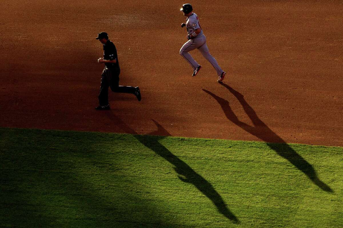 On a day and night that saw plenty of rounding the bases by both teams, Astros catcher Chris Snyder gets his trot on after homering in the fourth inning of Monday's second game. Casting a shadow with Snyder is umpire Tim Timmons.