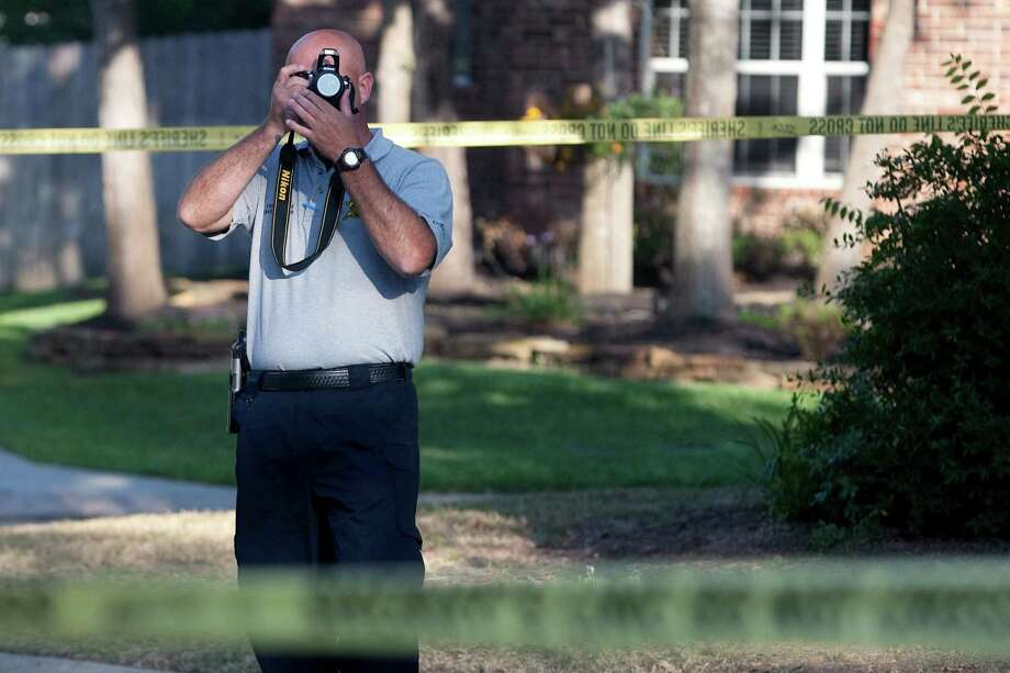 A Montgomery County Sheriff's detective takes pictures around the scene of an alleged murder-suicide on Monday, May 28, 2012, in The Woodlands, Texas. (AP Photo/The Courier, Karl Anderson) Photo: Karl Anderson, Associated Press / AP