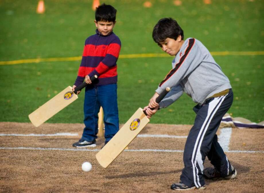 Ibrahim Zia, 8, right, of Darien, and Sufiyan Sabir, 5, left, of Stamford, play cricket in Lione Park in Stamford, Conn. on Saturday, Nov. 21, 2009. Photo: Chris Preovolos / Stamford Advocate