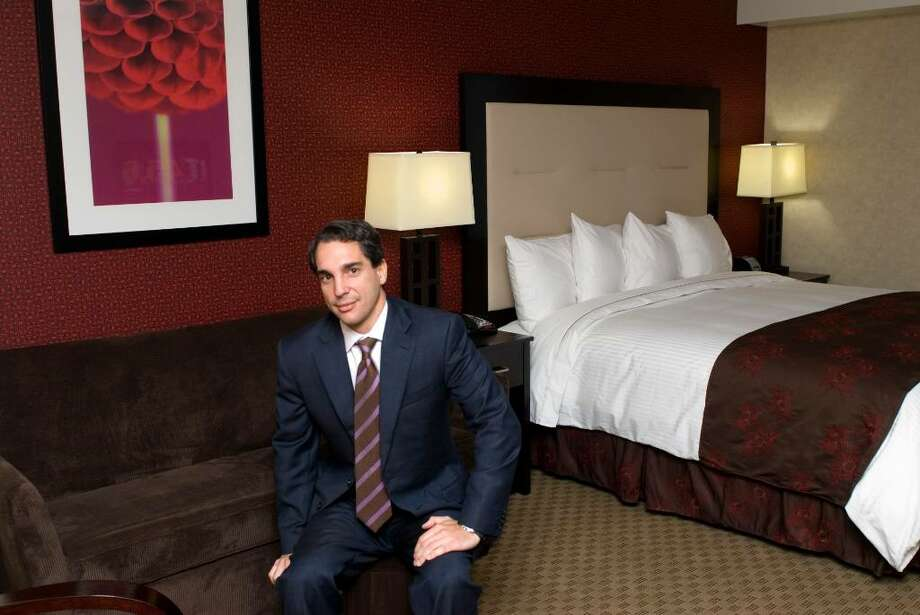 Randy Salvatore has opened a new hotel, Hotel Zero Degrees, at the old YMCA he sits in one of the rooms. Photo: Dru Nadler / Stamford Advocate