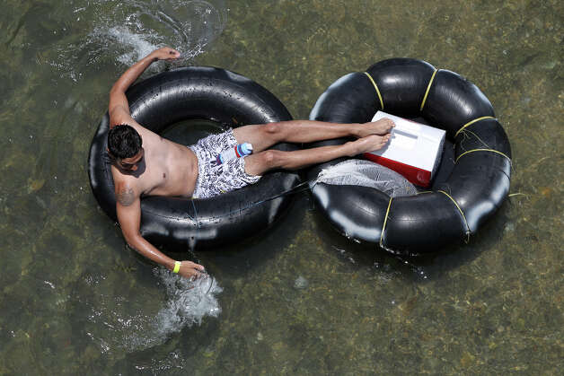 A tuber goes down the Comal river Memorial Day in New Braunfels. A new ban on disposable containers such as bottles and cans in the river is in place. Photo: San Antonio Express-News