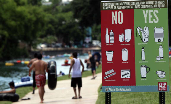 A sign informs Memorial Day visitors to Prince Solms Park in New Braunfels what is acceptable for tubers to carry down the Comal river. Disposable beverage containers such as beer cans are no longer allowed in the river in the city of New Braunfels. Photo: San Antonio Express-News