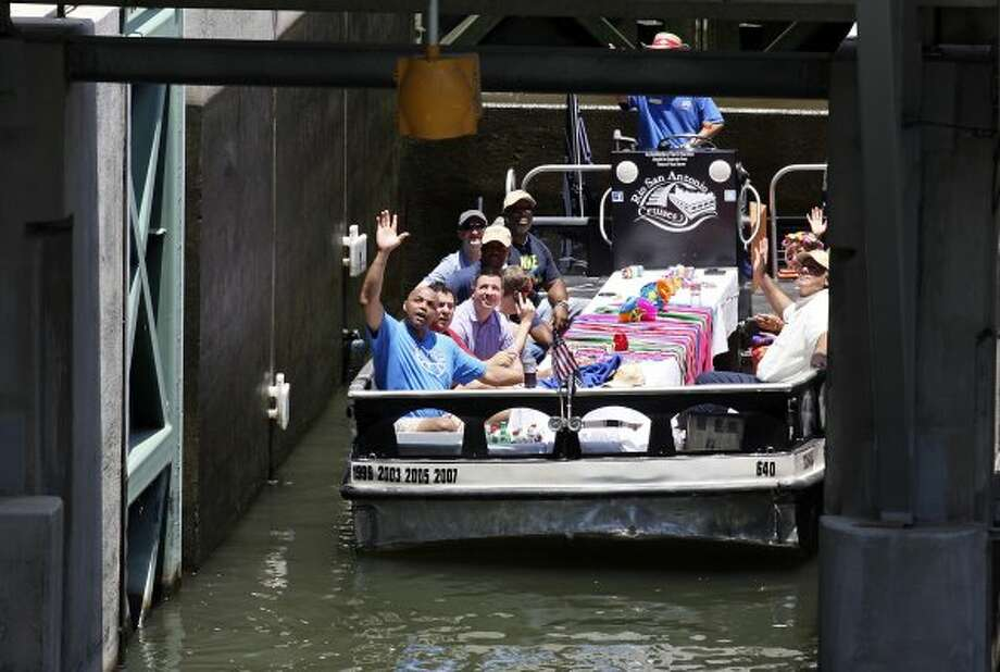 Basketball legend and TNT studio host Charles Barkley (left) waves to fans while on a barge passing through a lock on the Museum Reach section of the San Antonio River on Monday, May 28, 2012.