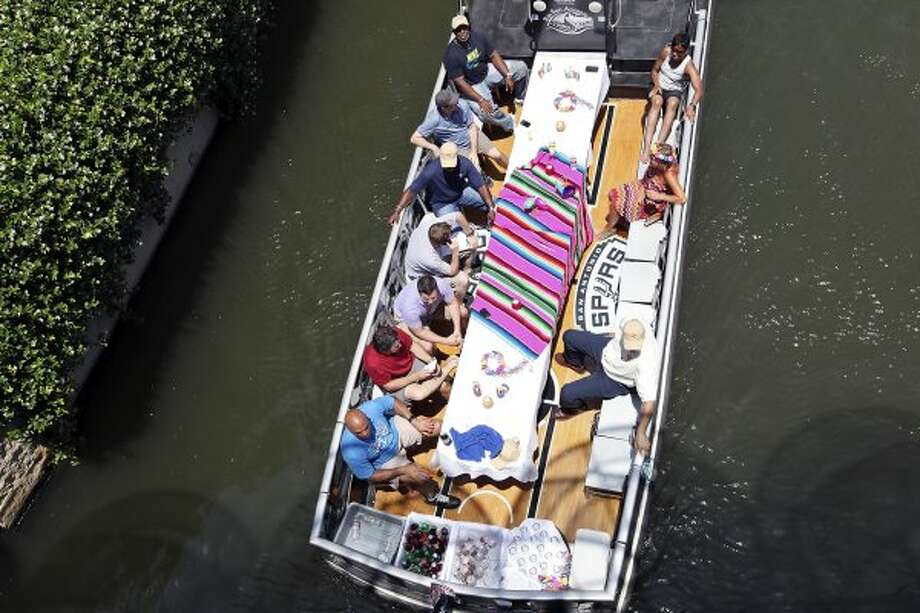 Basketball legend and TNT studio host Charles Barkley (left front) and others ride a barge on the Museum Reach section of the San Antonio River on Monday, May 28, 2012.