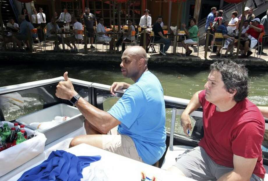 Basketball legend and TNT studio host Charles Barkley (left) gives a thumbs up to fans while on a River Walk tour with San Antonio Express-News columnist Roy Bragg on Monday, May 28, 2012.