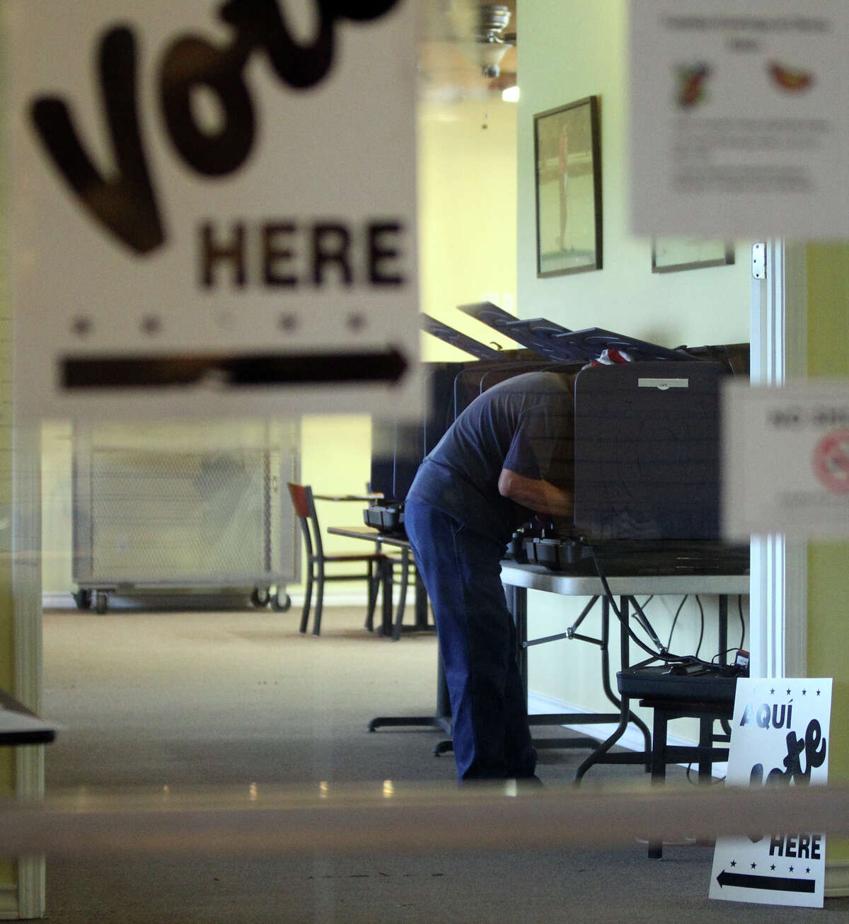 A man leans into a voting booth Tuesday, May 29, 2012, at the Olmos Basin Golf Course a few minutes after 7 a.m.