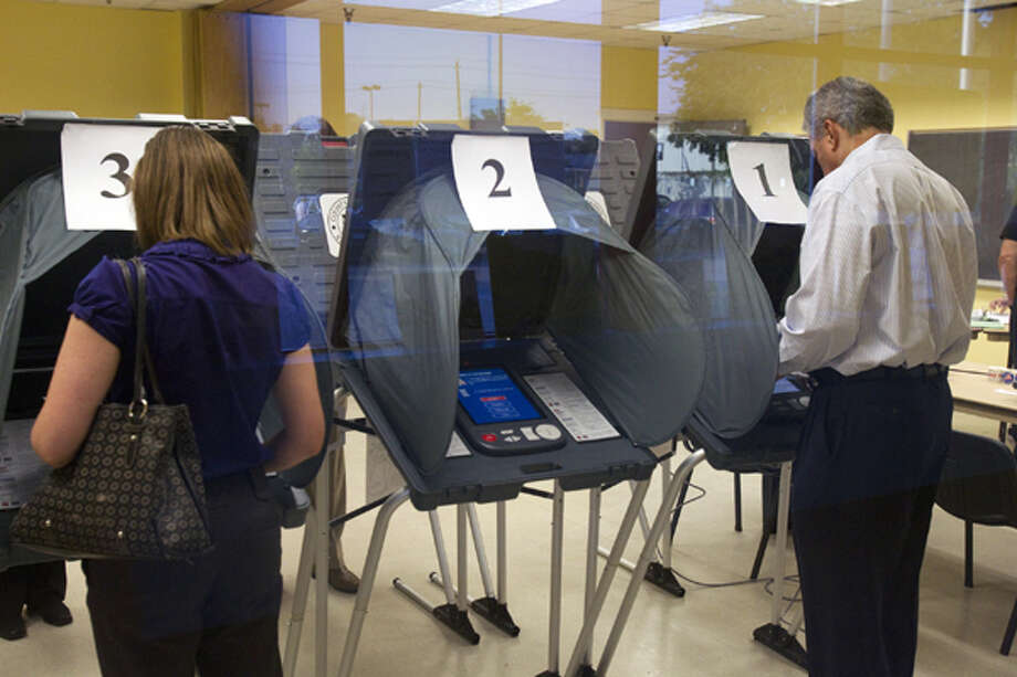 Julie Channell, left, and Michael Frey, right, cast their votes at the Metropolitan Multi-Services Center Tuesday, May 29, 2012, in Houston.  (Cody Duty / Houston Chronicle)