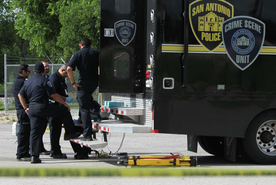 San Antonio police crime scene investigators examine a scene on the 4000 block of Interstate 35 north between Splashtown and Binz Engleman where a woman's body was found in a parking lot next to the Paradise for Gentlemen Club. Police said there was no visible trauma on the body. Photo: San Antonio Express-News