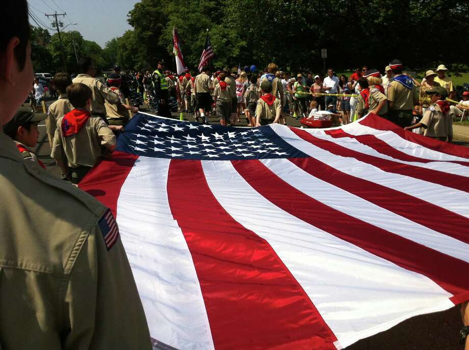 Darien Boy Scouts honor fallen heroes with a large American flag as they march down Post Road in the Memorial Day Parade, Monday, May 28, 2012. Darien, Conn. Photo: Thomas Michael