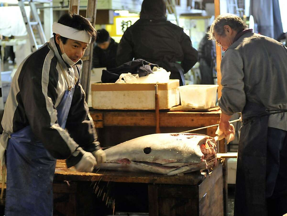 Fishmongers prepare a bluefin tuna at Tokyo's Tsukiji fish market in this March 23, 2011 file photo. Bluefin tuna caught off the US coast have been found to contain radioactive material from Japan's quake-struck Fukushima nuclear plant, according to a new study.Researchers found