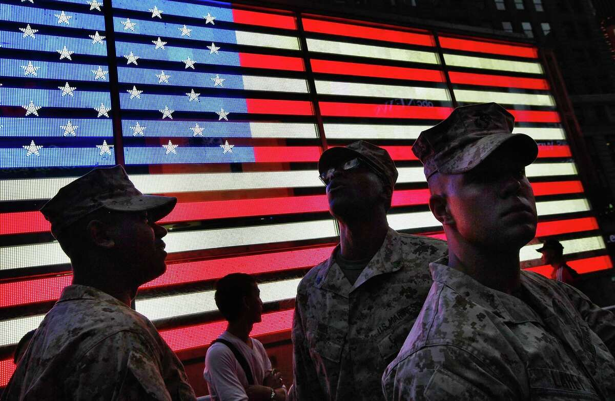 NEW YORK, NY - MAY 26: U.S. Marines look on in front of a lighted American flag in Times Square during Fleet Week festivities on May 26, 2012 in New York City. Fleet week, which has been held in New York City since 1984, celebrates the U.S. Navy and Marines Corps with a week of ship visitations and military demonstrations. Fleet Week concludes on Memorial Day with a military flyover to honor those killed while serving in the military. (Photo by Mario Tama/Getty Images) ***BESTPIX***