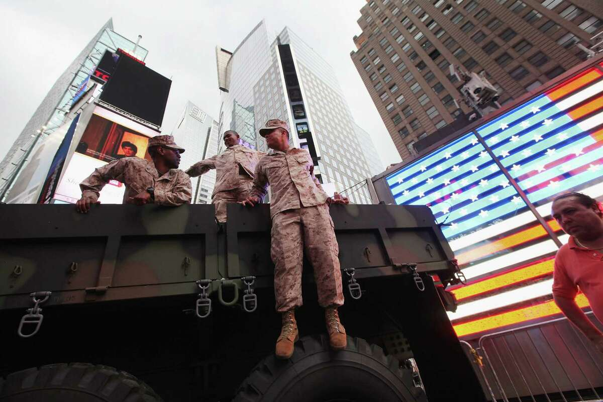 NEW YORK, NY - MAY 26: U.S. Marines gather on a military vehicle in Times Square during Fleet Week festivities on May 26, 2012 in New York City. Fleet week, which has been held in New York City since 1984, celebrates the U.S. Navy and Marines Corps with a week of ship visitations and military demonstrations. Fleet Week concludes on Memorial Day with a military flyover to honor those killed while serving in the military.