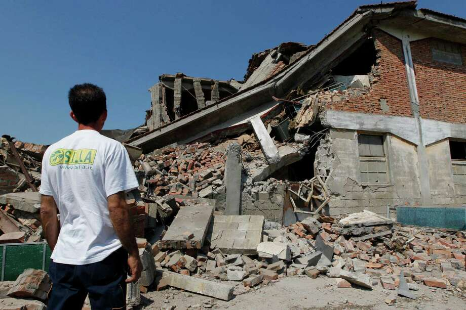 A man looks at a collapsed farm in Camposanto, northern Italy, Tuesday, May 29, 2012. A magnitude 5.8 earthquake struck the same area of northern Italy stricken by another fatal tremor on May 20.  (AP Photo/Luca Bruno) Photo: Luca Bruno, Associated Press / AP
