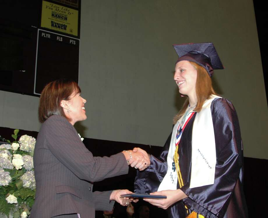 School board immediate past-president Carol Kendall-Keller hands Smithson Valley High salutatorian Anna Mayfield her diploma during Saturday's ceremonies. Photo: Photo By Sam Roberts