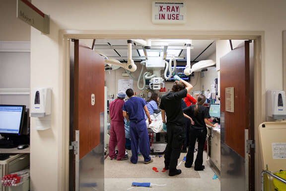 Doctors and other medical personnel worked in a crowded trauma room to care for a patient who arrived by helicopter at Memorial Hermann Hospital in 2012.