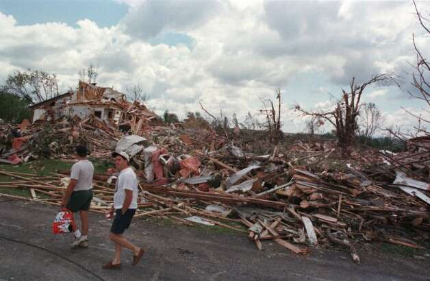 Ernie Zecca, LEFT, and Peter Enzien Jr., RIGHT, are surrounded by destruction as they walk up Sirchia Rd. where homes use to sit in Mechanicville. The tornado struck May 31, 1998.  (Albany Times Union)