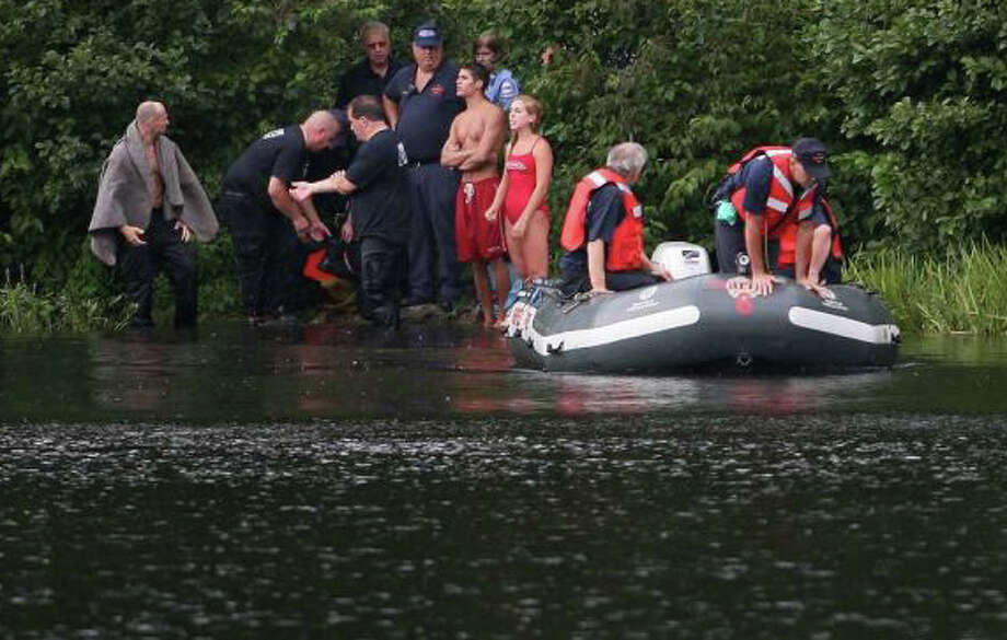 Emergency-services personnel, in this Fairfield Citizen file photo, are shown searching for the body of a man who drowned last August in Lake Mohegan. Photo: File Photo / Fairfield Citizen