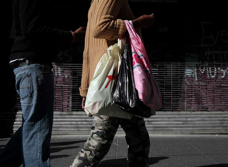 In this May 6, 2012, photo, shoppers carry their purchases along 33rd Street in New York. Americans' confidence in the economy in May had its biggest drop in eight months as consumers fretted about slow hiring, a big stock market drop and the global economy, according to the Conference Board, a private research group. Consumer confidence is widely watched because consumer spending accounts for 70 percent of economic activity. (AP Photo/CX Matiash) Photo: CX Matiash / AP2012