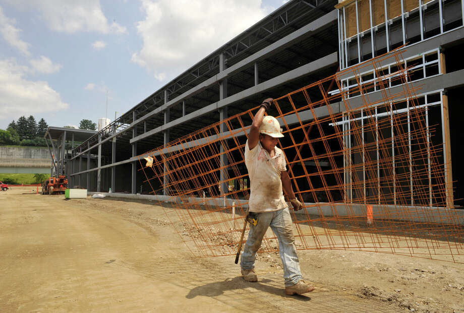 Jose Moreno, with SJS Concrete Works, carries reinforcement bars along the front of what will become The Shops at Marcus Dairy in Danbury, Conn., on Tuesday, May 29, 2012. Photo: Jason Rearick / The News-Times