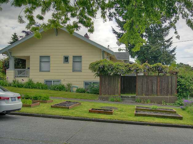 Raised garden beds of 3003 44th Ave. S.W. The 1,580-square-foot house has three bedrooms, 1.75 bathrooms, built-in shelves in the living room, a 'shabby chic' kitchen with open shelves and a tile floor, a lower-level family room, and a backyard deck and patio on the 3,234-square-foot corner lot. It's listed for $349,000, although a sale is pending. Photo: Courtesy Barb Hunsinger/Windermere Real Estate