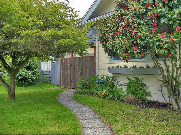 Yard of 3003 44th Ave. S.W. The 1,580-square-foot house has three bedrooms, 1.75 bathrooms, built-in shelves in the living room, a 'shabby chic' kitchen with open shelves and a tile floor, a lower-level family room, a backyard deck and patio and raised garden beds on the 3,234-square-foot corner lot. It's listed for $349,000, although a sale is pending. Photo: Courtesy Barb Hunsinger/Windermere Real Estate