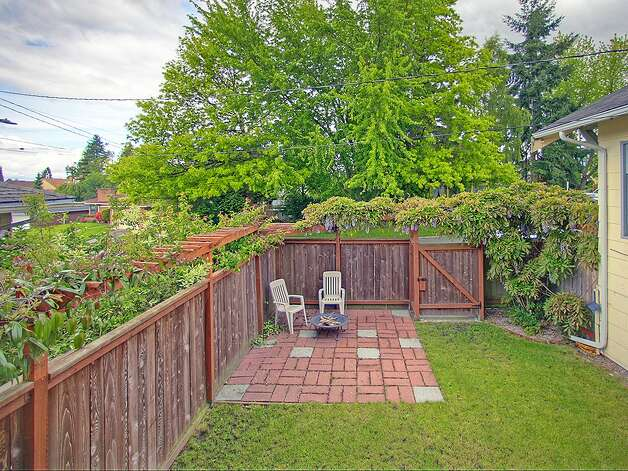 Backyard, with patio, of 3003 44th Ave. S.W. The 1,580-square-foot house has three bedrooms, 1.75 bathrooms, built-in shelves in the living room, a 'shabby chic' kitchen with open shelves and a tile floor, a lower-level family room, a backyard deck and raised garden beds on the 3,234-square-foot corner lot. It's listed for $349,000, although a sale is pending. Photo: Courtesy Barb Hunsinger/Windermere Real Estate