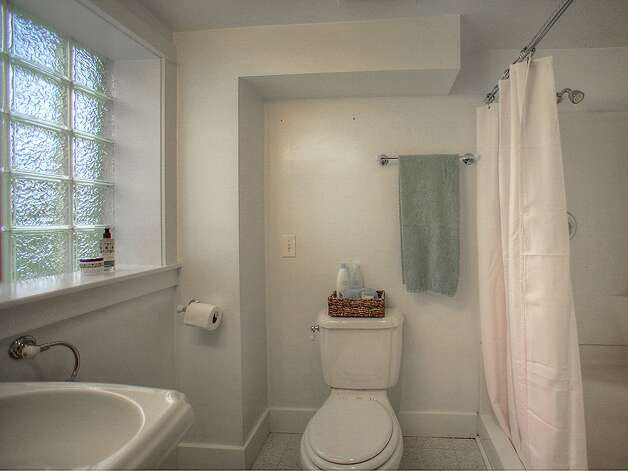 Three-quarter bathroom of 3003 44th Ave. S.W. The 1,580-square-foot house has three bedrooms, 1.75 bathrooms, built-in shelves in the living room, a 'shabby chic' kitchen with open shelves and a tile floor, a lower-level family room, a backyard deck and patio and raised garden beds on the 3,234-square-foot corner lot. It's listed for $349,000, although a sale is pending. Photo: Courtesy Barb Hunsinger/Windermere Real Estate