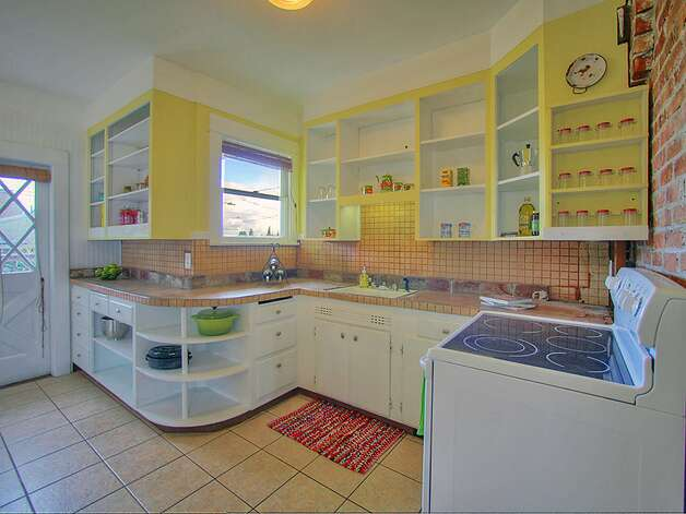 'Shabby chic' kitchen, with open shelves and a tile floor, of 3003 44th Ave. S.W. The 1,580-square-foot house has three bedrooms, 1.75 bathrooms, built-in shelves in the living room, a lower-level family room, a backyard deck and patio and raised garden beds on the 3,234-square-foot corner lot. It's listed for $349,000, although a sale is pending. Photo: Courtesy Barb Hunsinger/Windermere Real Estate