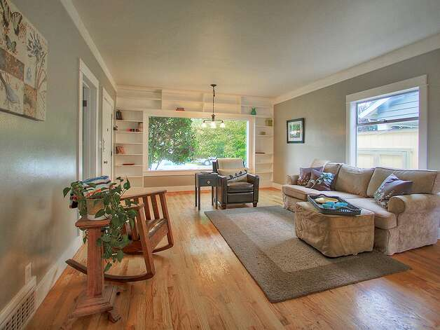 Living room, with built-in shelves, of 3003 44th Ave. S.W. The 1,580-square-foot house has three bedrooms, 1.75 bathrooms, a 'shabby chic' kitchen with open shelves and a tile floor, a lower-level family room, a backyard deck and patio and raised garden beds on the 3,234-square-foot corner lot. It's listed for $349,000, although a sale is pending. Photo: Courtesy Barb Hunsinger/Windermere Real Estate