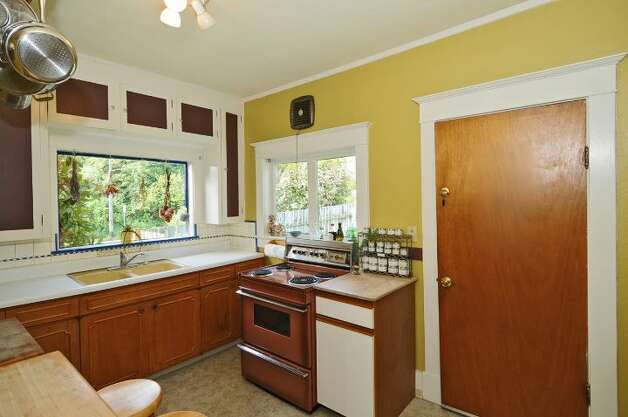 Kitchen of 2659 49th Ave. Court S.W. The 2,080-square-foot home, built in 1911, has two bedrooms, 1.75 bathrooms, built-in cabinets, crown moldings, a basement rec room, a fenced front garden, and a back patio on a 4,830-square-foot lot. It's listed for $399,900. Photo: Courtesy John Pettas/Windermere Real Estate