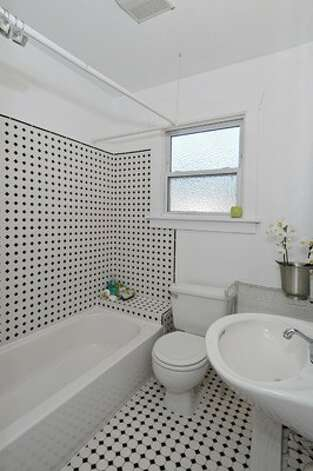 Bathroom of 3805 S.W. Admiral Way. The 710-square-foot house, built in 1919, has two bedrooms, one bathroom, French doors, a gas fireplace, parking for three cars and a storage shed on a 3,200-square-foot lot. It's listed for $350,000. Photo: Courtesy Terry Miller/Coldwell Banker Bain